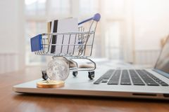 Business and finance concept, Close up shopping cart with credit card and bitcoin on desk for E-Commerce online shopping.  stock photos