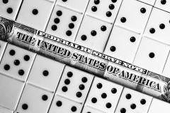 Business and finance concept - dominoes and us dollar. Stock Photos