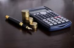 Business and Finance concept with Fountain pen and Calculator mo. Ney coins stack royalty free stock image