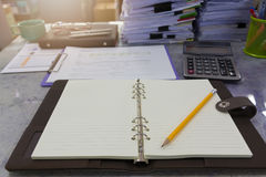 Business and finance concept of office working, Opened blank notebook and pencil with pile of unfinished documents. Background Royalty Free Stock Image
