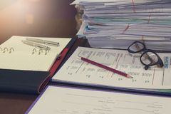 Business and finance concept of office working, Pile of unfinished documents on office desk, Closeup pencil with stack. Of business paper Royalty Free Stock Image