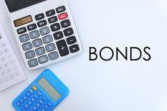 Business and finance concept. Top view of calculator on white background written with BONDS royalty free stock image