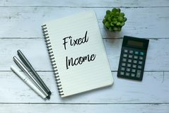 Business and finance concept. Top view of plant,calculator,pen and notebook written with Fixed Income. stock photo