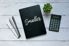 Business and finance concept.Top view of plant,calculator,pen and notebook written with Smaller. Business and finance concept.Top view of plant,calculator,pen stock photography