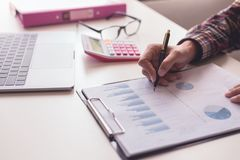 Businessman check about cost and doing finance graph report at office. Business and finance investment concept : Businessman check about cost and doing finance Royalty Free Stock Images