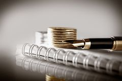Business, finance or investment concept. Coins, cheque book or note book and fountain pen. Light toned background. stock image