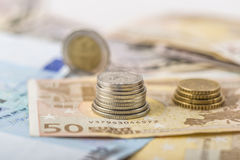 Business, finance, investment, saving and cash concept - close up of euro paper money and coins on table Royalty Free Stock Image