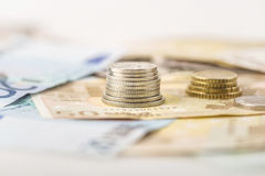 Business, finance, investment, saving and cash concept - close up of euro paper money and coins on table Stock Photos