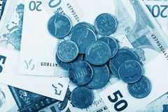 Business, finance, investment, saving and cash concept - close up of euro paper money and coins on table Stock Photo
