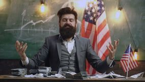 Business, finance, luck, fortune and people concept. Blurred portrait of a man in a suit against the background of the. American flag with packs of money in stock footage