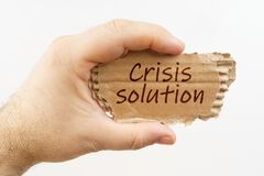 A man holds a cardboard in his hand on which it is written - Crisis solution