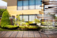 Business finance and real estate concepts. Business finance and real estate concepts,  Empty wood table top, Money coin stack with blurred home garden Stock Image