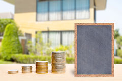 Business finance and real estate concepts. Business finance and real estate concepts, Money coin stack with chalkboard free space for you planing, Blurred home Royalty Free Stock Photography