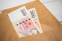 business, finance, saving, banking concept - close up bundle of money Czech koruna in envelope on wooden table royalty free stock photography