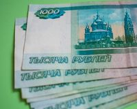 finance, saving, banking, concept - close up bundle of money Russian Banknotes thousand rubles on green background stock photography