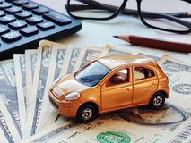 Miniature car model, calculator, dollar money and saving account book or financial statement on office desk table. Business, finance, saving money, banking or Stock Image