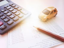 Miniature car model, calculator and saving account book or financial statement on office desk table. Business, finance, saving money, banking or car loan concept Royalty Free Stock Photo