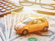 Miniature car model, calculator and saving account book or financial statement on office desk table. Business, finance, saving money, banking or car loan concept Royalty Free Stock Photography