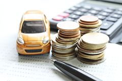 Miniature car model, coins stack, calculator and saving account book or financial statement on office desk table. Business, finance, saving money, banking or car Stock Image