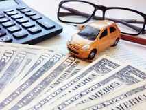 Miniature car model, calculator, dollar money, eyeglasses, pencil and saving account book or financial statement on office desk Stock Photos