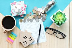Top view or flat lay of wood house model, saving account book or financial statement and coins on office desk table. Business, finance, saving money, property Royalty Free Stock Photography