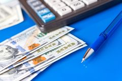 Business and financial background with dollars, pen and calculator. Bookkeeping background. stock photos