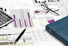 Business financial chart analysis with pen, eyeglasses, calculat Stock Photos