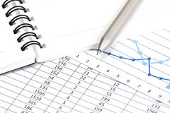 A business financial chart with a pen pointing at Stock Images