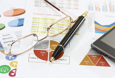 Business and financial. Closeup image of graphics and finance report for business with pen mobile phone and coffee Stock Photography