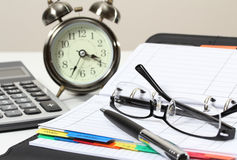 Business and financial. Closeup image of pen book calculator and clock on desk for working Stock Photo
