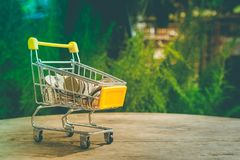 Various money coins Baht in yellow mini shopping cart or supermarket trolley. Business and Financial Concept : Various money coins Baht in yellow mini shopping Stock Photography