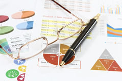 Business and financial. Image of graphics and finance report for business with pen and glasses Royalty Free Stock Images