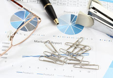 Business and financial. Image of graphics and finance report for business with pen glasses paper clips and stapler Royalty Free Stock Image