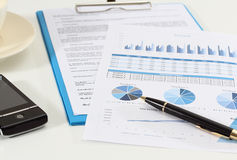 Business and financial. Image of graphics and finance report for business with pen mobile phone and coffee Stock Image