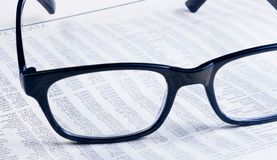 Business financial newspaper report see through glasses lens, workplace of the businessman Stock Image