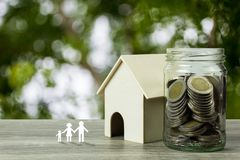 Business and financial property concept for home loan, mortgage, saving and investment. A small house model with stack of coins in. Glass jar and family in stock image