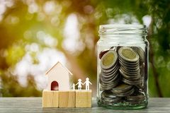 Business and financial property concept for home loan, mortgage, saving and investment. A small house model with stack of coins in glass jar on wooden table royalty free stock image