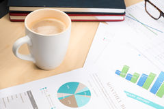 Business and financial report with coffee.Graph,book,glasses,Document is mockup Royalty Free Stock Photo