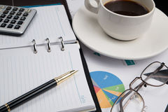 Business and financial report with pen and calculator on wooden table.coffee Stock Photography