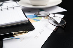 Business and financial report with pen and calculator on wooden table.coffee Royalty Free Stock Photo