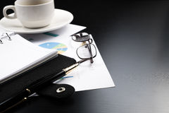 Business and financial report with pen and calculator on wooden table.coffee Royalty Free Stock Photography