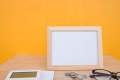 Business on financial report . photo Frame and coin on a wooden. On Yellow background stock photos