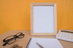 Business on financial report . photo Frame and coin on a wooden. On Yellow background stock photography