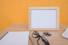 Business on financial report . photo Frame and coin on a wooden. On Yellow background stock photo