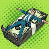 Business financial success concept businessman. At the stack of money pop art retro style. The salary of the joy of work. Financial success Stock Images