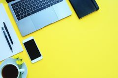 Business flat lay: desk with notebook, pencil, cup of coffee on yellow table. Copy space. Business flat lay: desk with notebook, pencil, cup of coffee on yellow royalty free stock photo