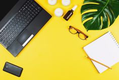 Business flatlay with laptop, mobile phone, glasses, philodendron leaf, candles, cream, pen and notebook. Concept of a woman`s work place. Flat lay. Yellow stock photo