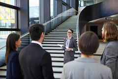 Business forum guide giving tour to participants. Smiling confident business forum guide with badge on neck standing on stairs and holding clipboards with files royalty free stock photo