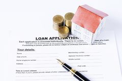 Business fountain pen and coins stack and house paper on loan application stock image