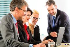 Businesspeople looking at laptop screen Stock Photo
